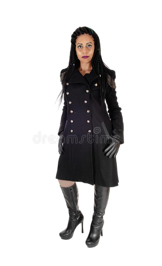 Young woman standing in black coat and boots royalty free stock photos