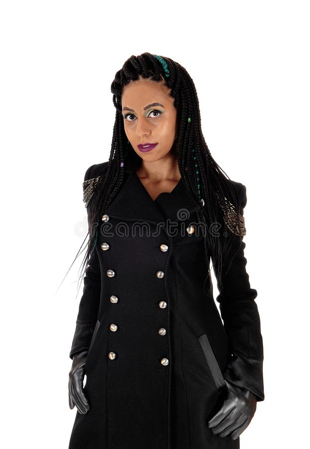 Young woman standing in black coat and cloves royalty free stock photo
