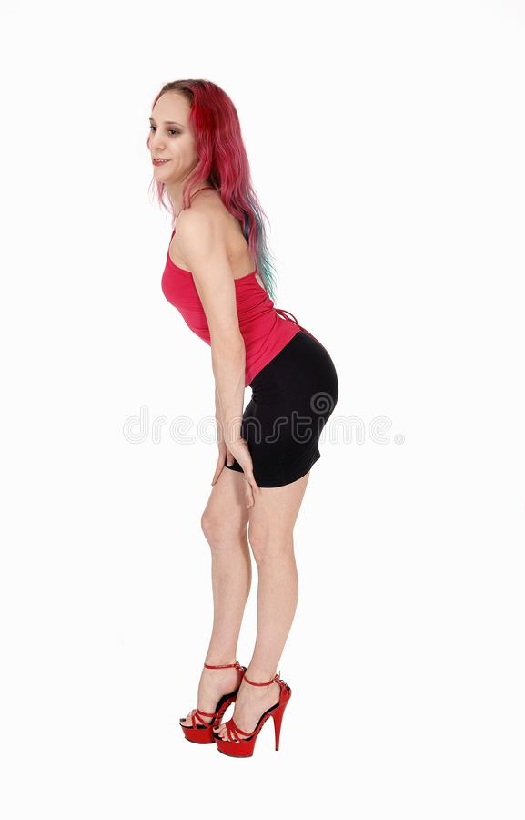 Young woman standing in a black skirt and red blouse bending. A lovely young woman standing in a black skirt and red top with.her red hair, smiling, isolated for stock photos