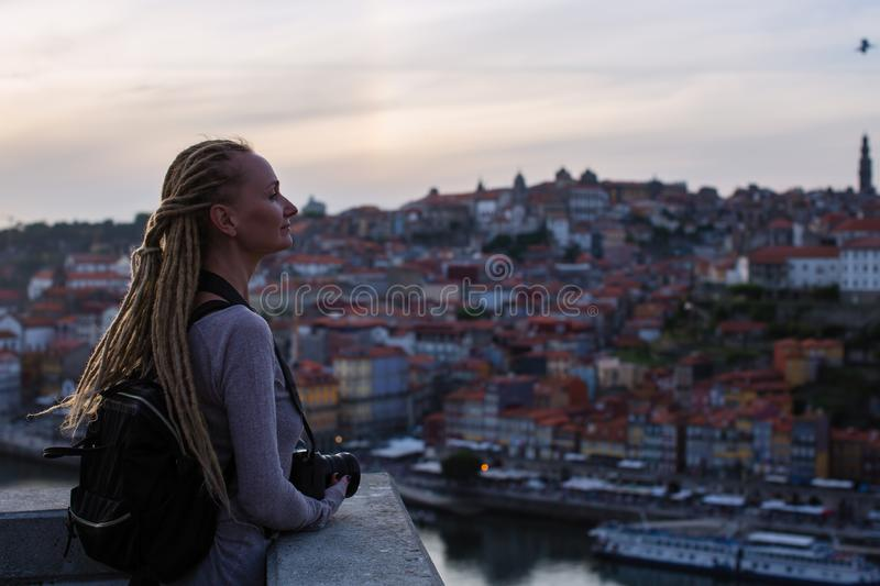 Young woman standing with camera in old town during dusk, Porto, Portugal. royalty free stock images