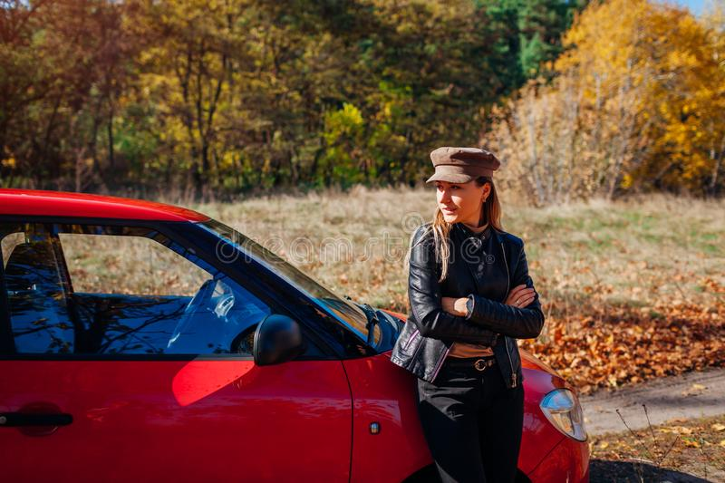 Young woman standing by car on autumn road. Driver stopped auto in forest to enjoy fall landscape royalty free stock image