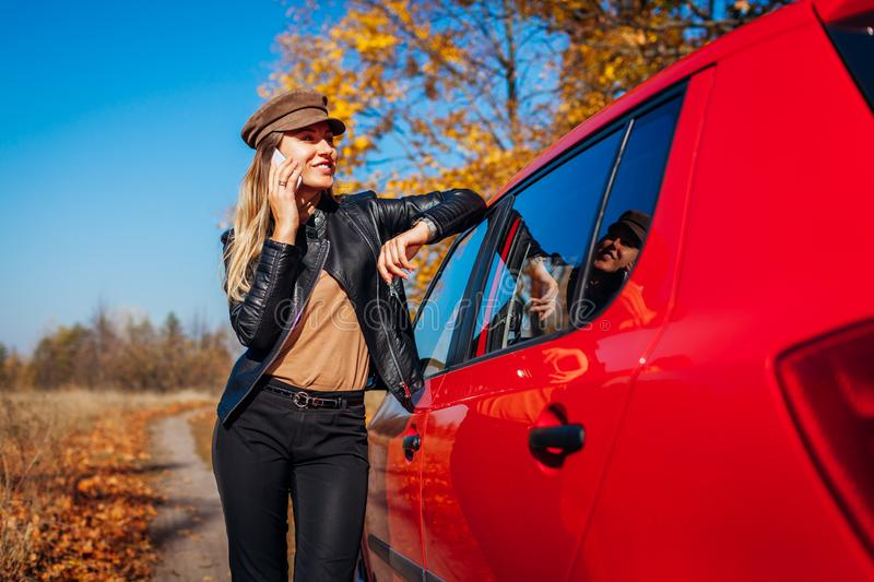 Young woman standing by car using smartphone on autumn road. Driver stopped auto in forest to call royalty free stock images