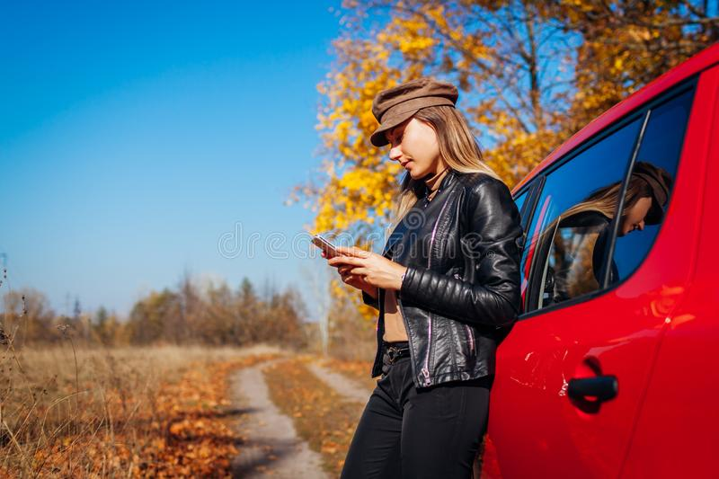 Young woman standing by car using smartphone on autumn road. Driver stopped auto to catch better signal stock photography
