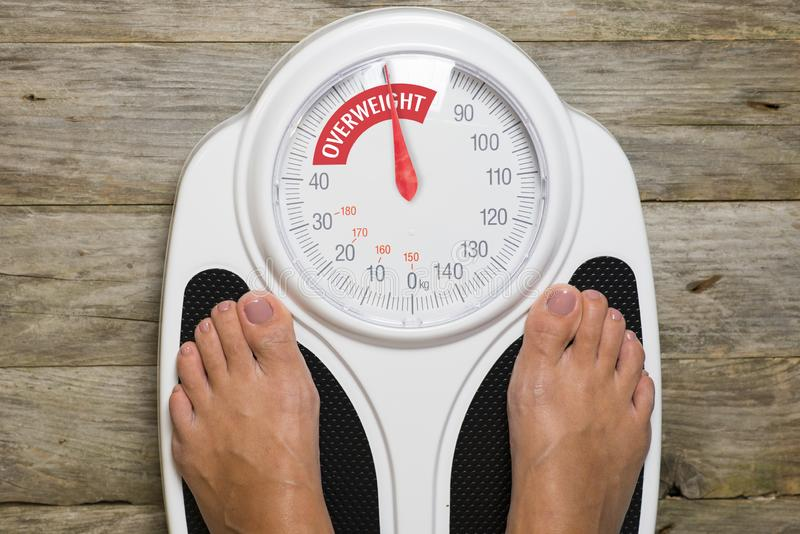 Young woman standing on classic analogue weight scale indicating overweight stock image