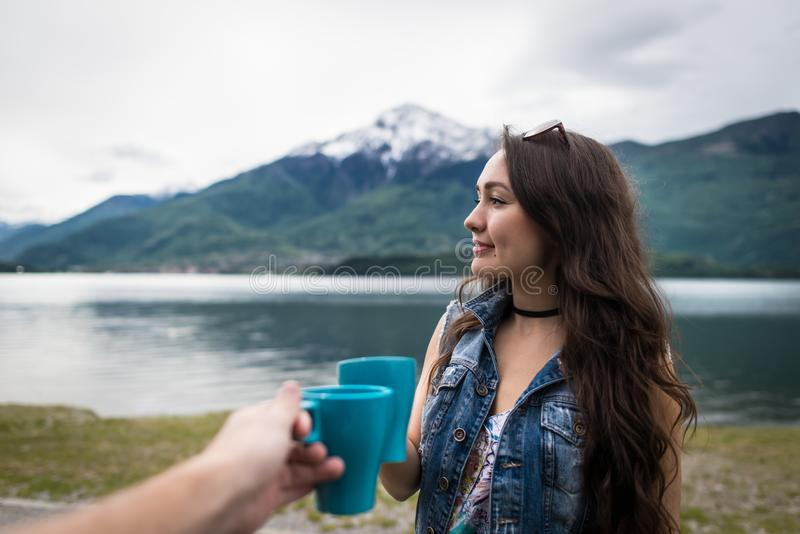 Young woman standing with cup of coffee in morning. On background of mountains and lake in Como, Italy. Smiling girl celebrate holidays with boyfriend stock images