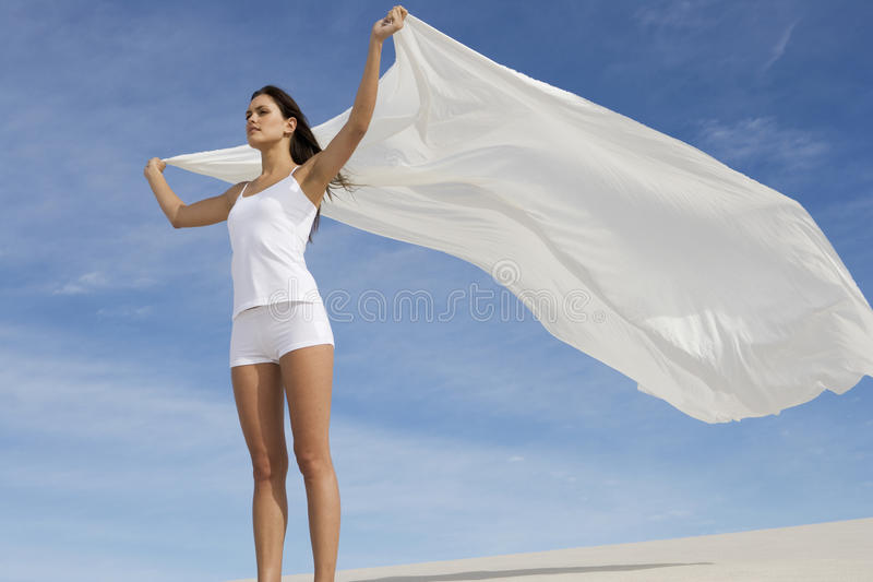 A young woman standing in the desert with a sheet stock images