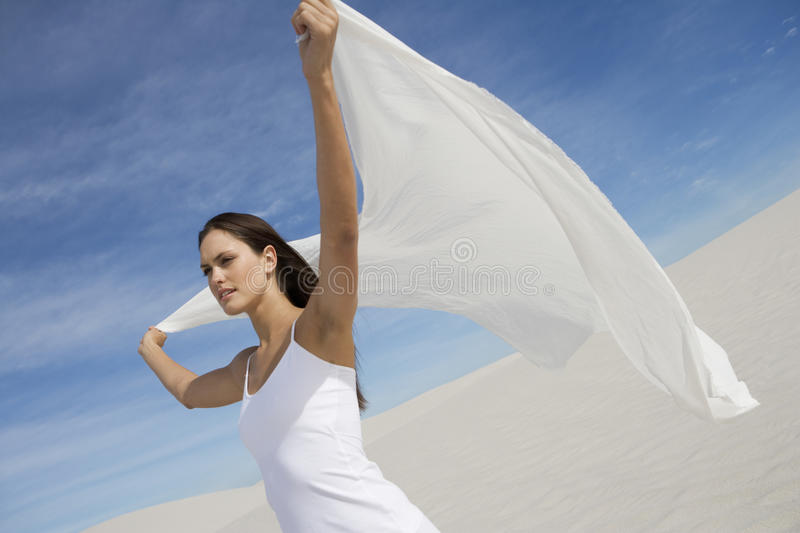 A young woman standing in the desert with a sheet stock photos
