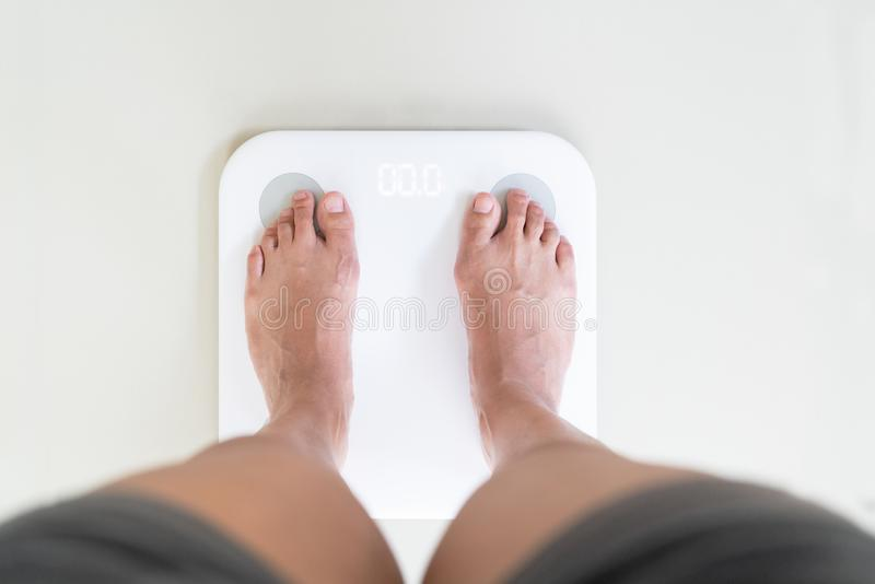 Young woman standing on digital weight scale royalty free stock images