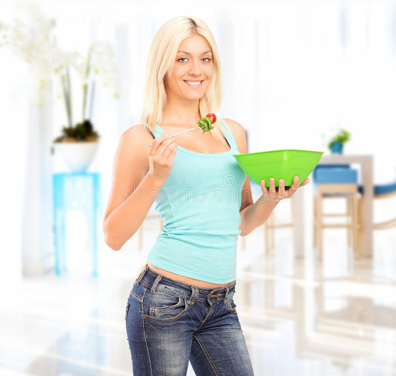 Download Young Woman Standing And Eating A Salad Royalty Free Stock Photography - Image: 26301977
