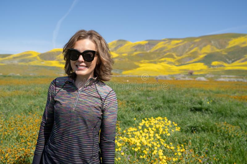 Young woman standing in a field poses during the super bloom at Carrizo Plain National Monument in California. Wearing sunglasses. And athleisure clothing stock photography