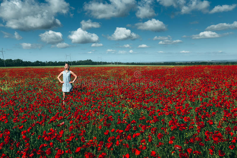 Young woman standing in the field of red poppies against the blue sky scenic landscape concept of outdoor recreation stock photography