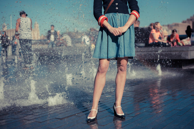 Young woman standing by fountain in city stock photo
