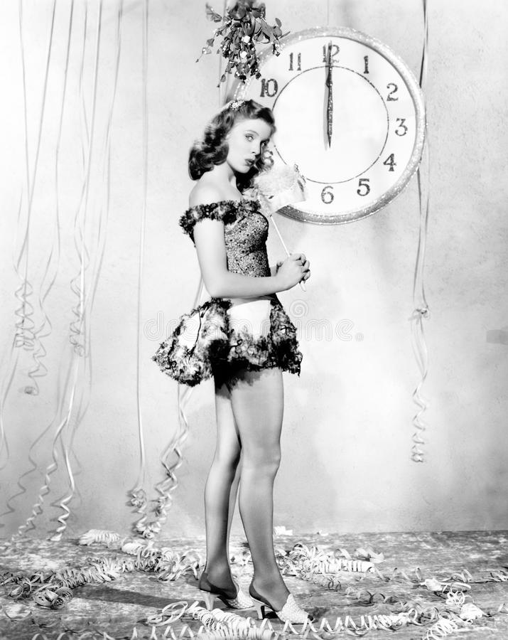 Young woman standing in front of a clock, celebrating New Years Eve royalty free stock photo