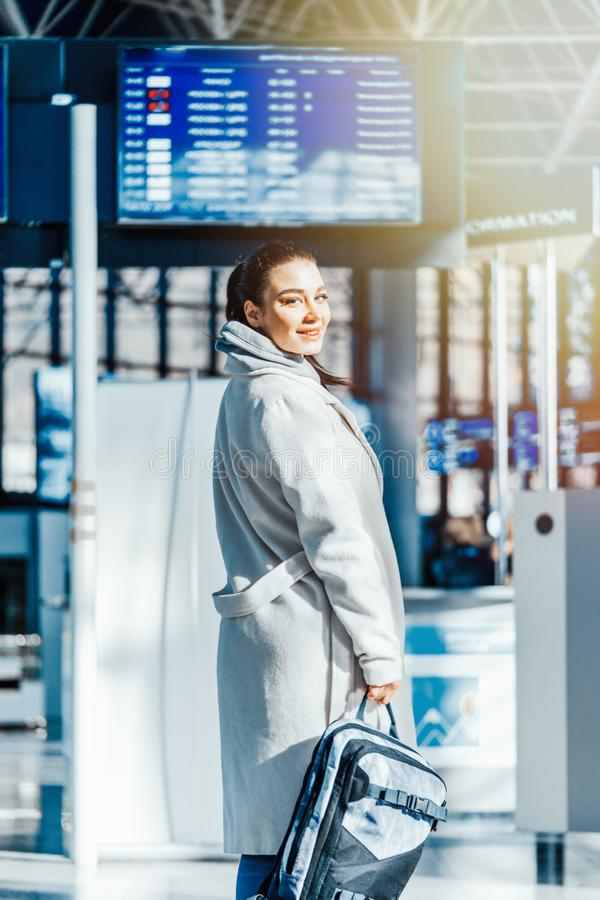 Young woman standing in front of Destination board and smiling in airport stock image