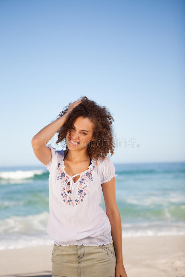 Young woman standing in front of the sea. With her hand on her head stock photography