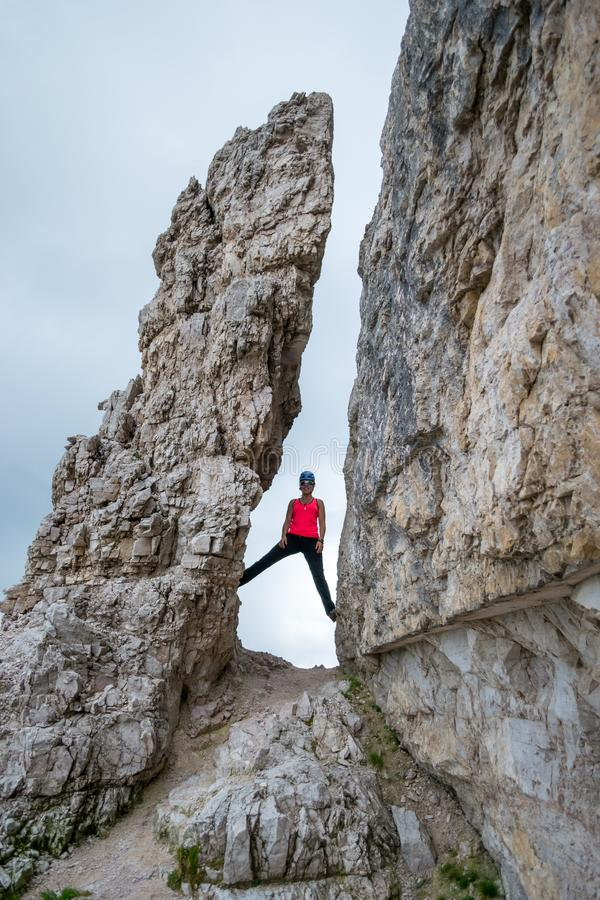Young woman standing high between two tall, vertical rocks, at the beginning of the via ferrata route towards Averau peak stock photo