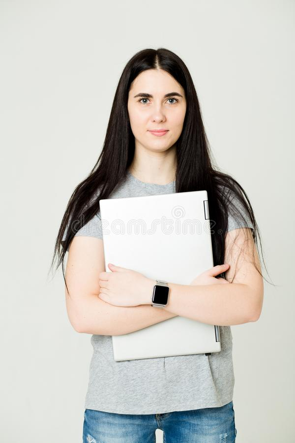 Young woman standing and holding laptop. Happy young girl using her laptop, isolated on white royalty free stock image