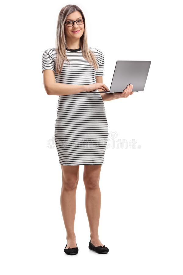 Young woman standing and holding an open laptop computer stock image