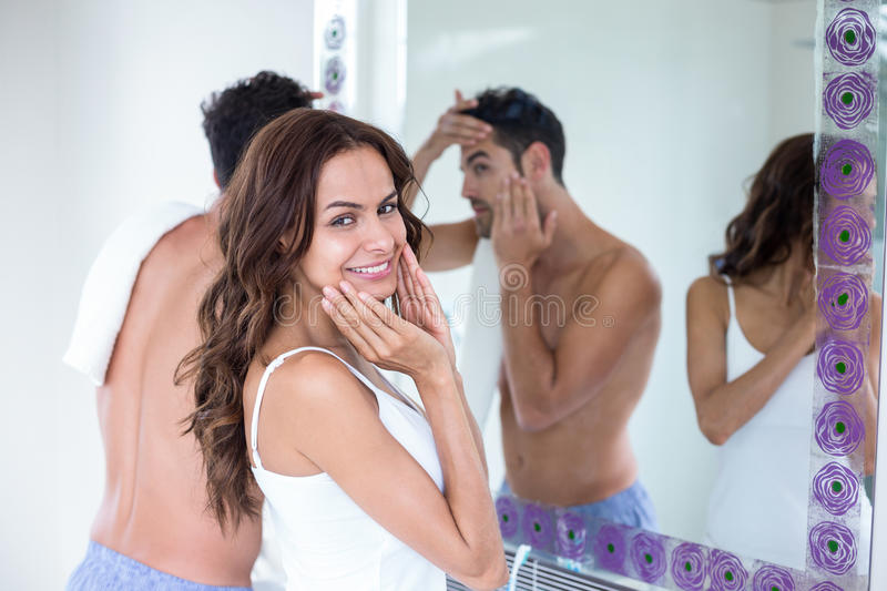 Young woman standing by husband in front of mirror stock photography