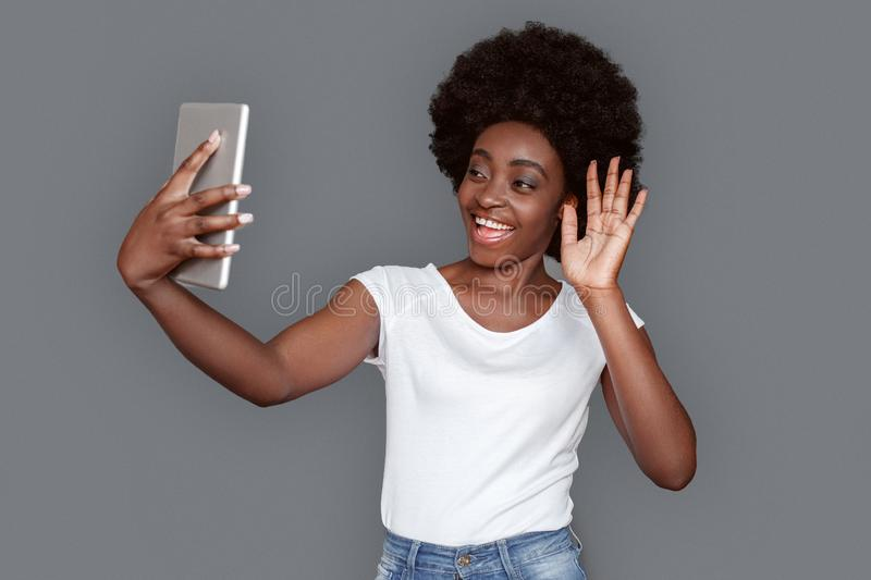 Young woman standing isolated on gray having video call on digital tablet smiling happy royalty free stock photography