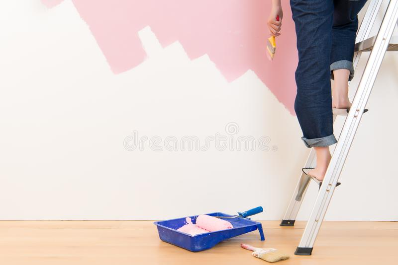 Young woman standing on ladder wall painting. Beautiful young woman standing on ladder doing wall painting. mixed race asian chinese female model royalty free stock photos