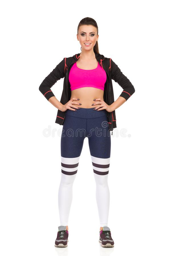 Young Woman Standing Legs Apart In Fitness Outfit. Front View. Young woman in fitness clothes is standing legs apart, looking at camera and holding hands on hip stock photos