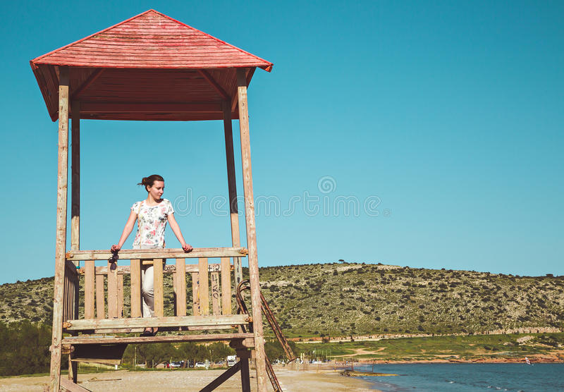 Young woman standing on lifeguard post. On a sunny day stock photos