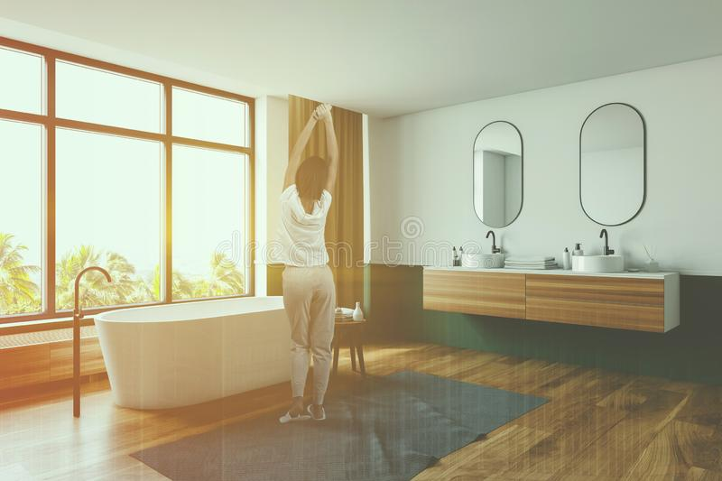 Woman in white and green bathroom with sink stock photos