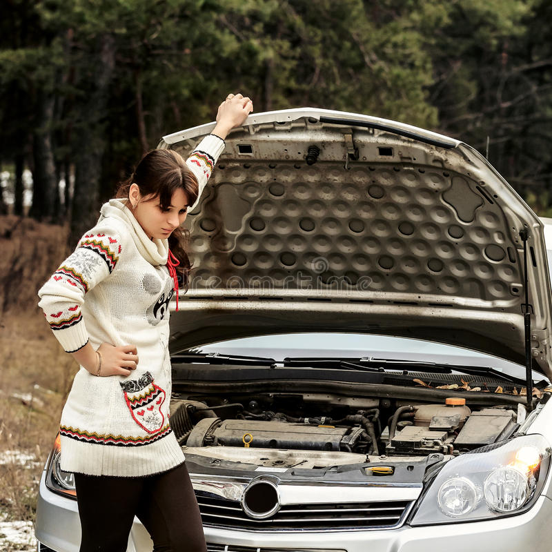 Young woman standing near the broken car. The girl opened the hood and look at the engine. Refit woman car. Young woman in a white jacket standing near the stock image