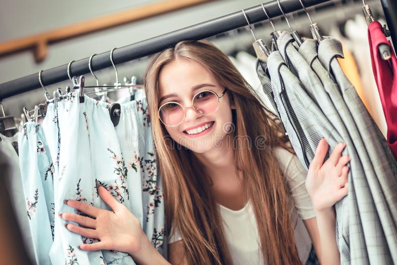 Young woman standing near clothes rack on color background stock photo