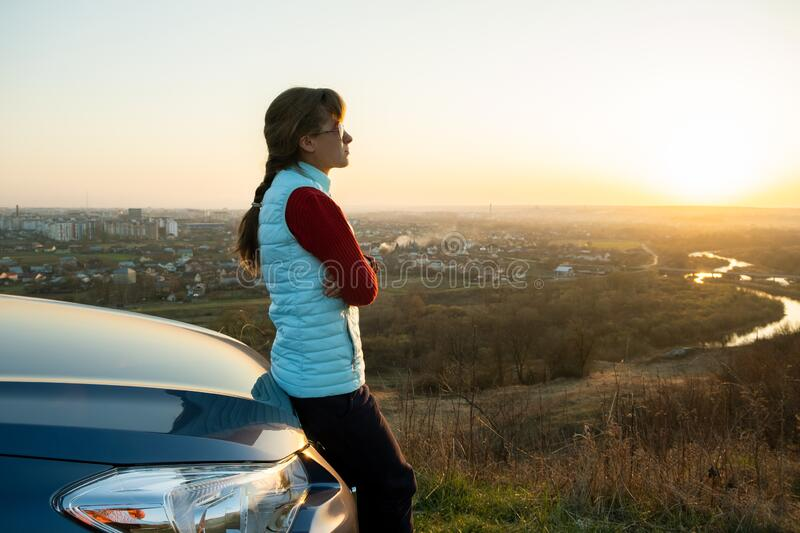 Young woman standing near her car enjoying warm sunset view. Girl traveler leaning on vehicle hood looking at evening horizon.  royalty free stock photography