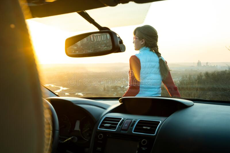 Young woman standing near her car enjoying warm sunset view. Girl traveler leaning on vehicle hood looking at evening horizon.  royalty free stock photo