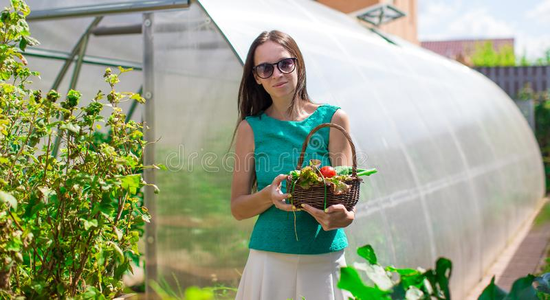Young woman standing near her greenhouse outdoors. With busket stock photo