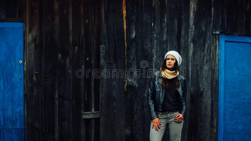 Young woman standing near old village house stock photo