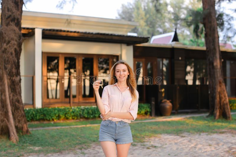 Young woman standing near resort house and keeping keys. royalty free stock photography