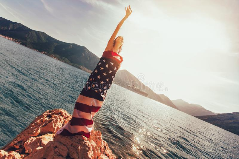 Young woman standing on the reef wrapped in American flag royalty free stock photos