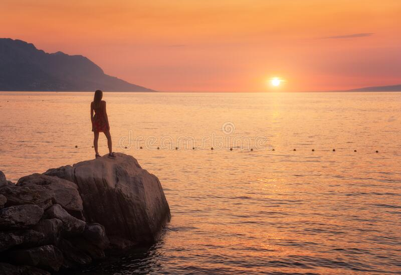 Young woman standing on the rock in the sea against mountains. And colorful orange sky at sunset in summer in Croatia. Landscape with alone slim girl on the stock photos