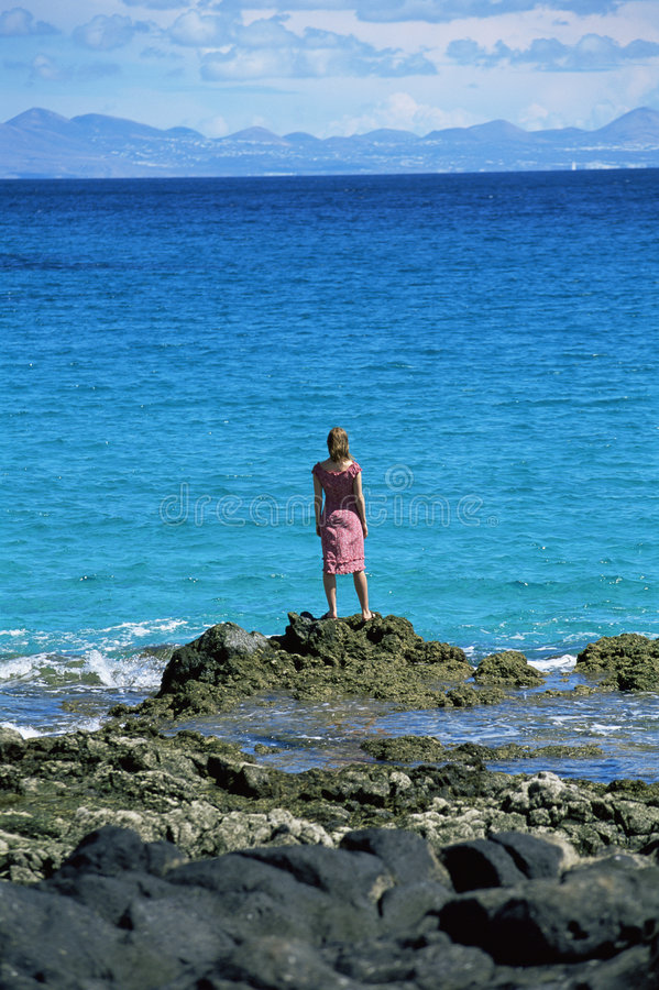 Free Young Woman Standing Rocks, Looking Out To Sea Stock Photo - 6078510