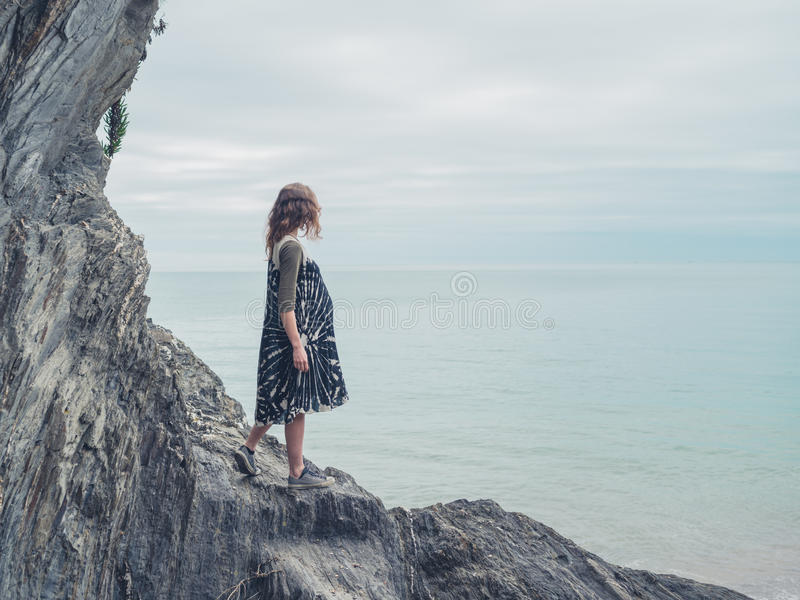 Young woman standing on rocks and looking at sea. A young woman is standing on some rock on the coast and is looking at the sea royalty free stock images