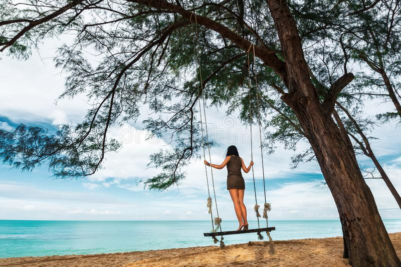Young woman standing on rope swing on tropical sandy beach on background of sea and blue sky stock image