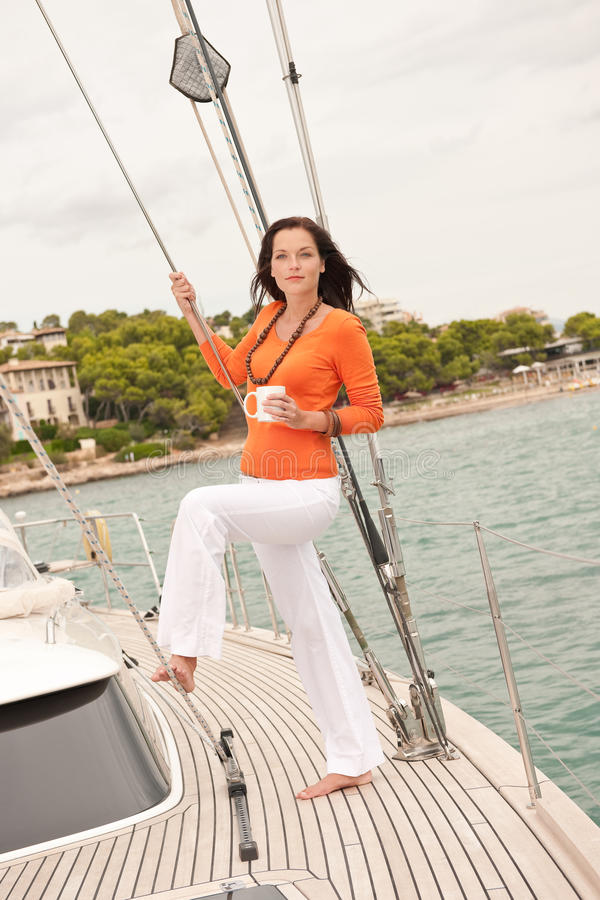 Young woman standing on sailing boat stock photo