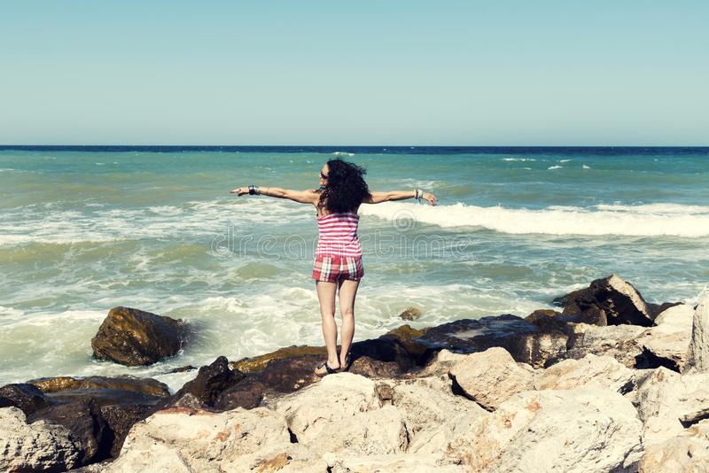 Young woman standing on a sea beach enjoying the beautiful sunny weather. Selective focus royalty free stock photos