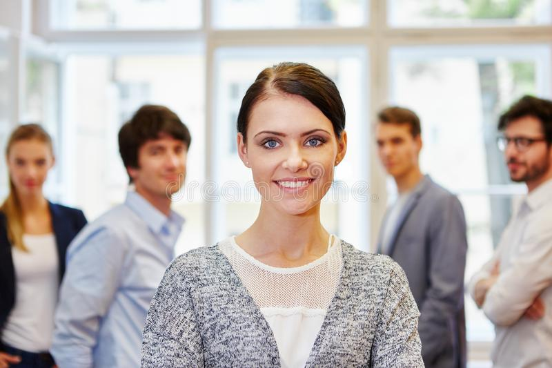 Young woman standing and smiling in front of team royalty free stock images