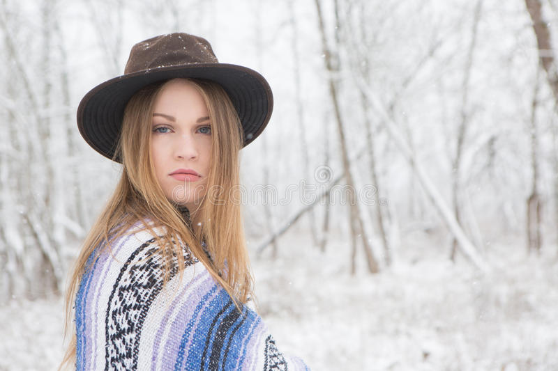 Young woman standing in snow with blanket and hat. royalty free stock photos