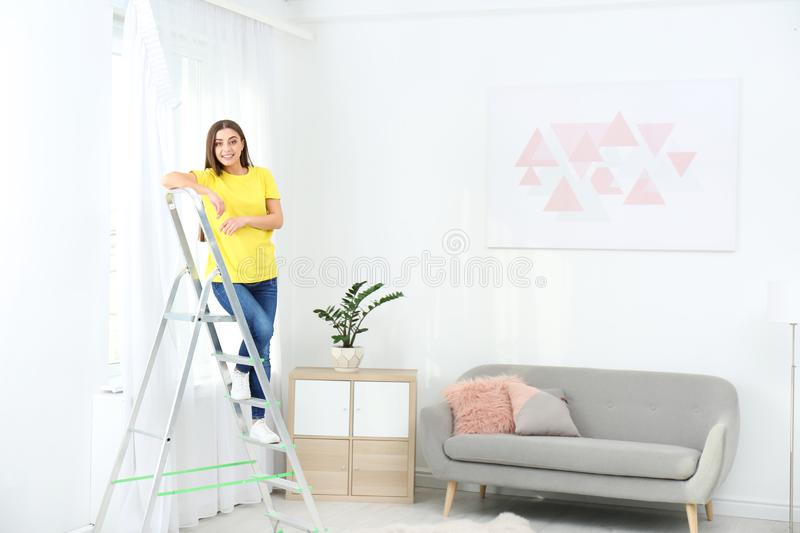 Young woman standing on stepladder near window with curtain in room. royalty free stock photography