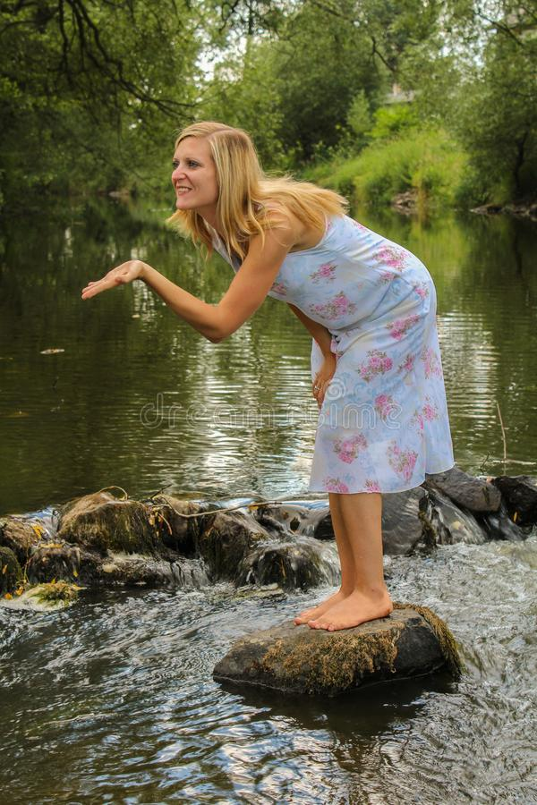 Young woman standing on stone in river, sending kiss royalty free stock photography