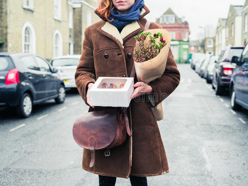 Young woman standing in street with cake and flowers royalty free stock images