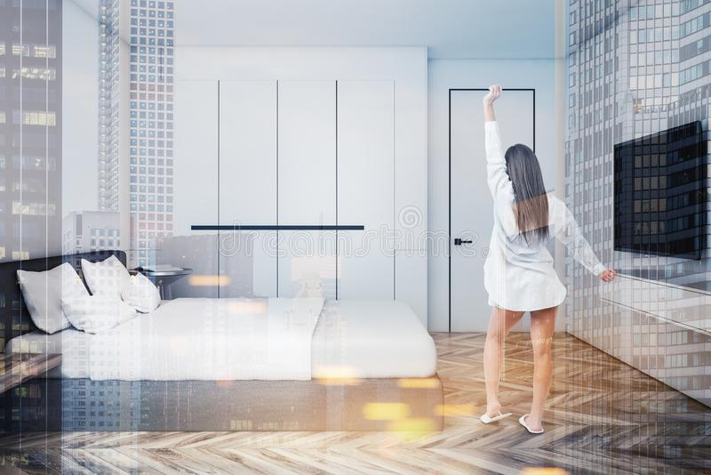 Woman in stylish bedroom with TV set. Young woman standing in stylish bedroom with white walls, wooden floor, master bed and TV set on the wall. Concept of royalty free illustration