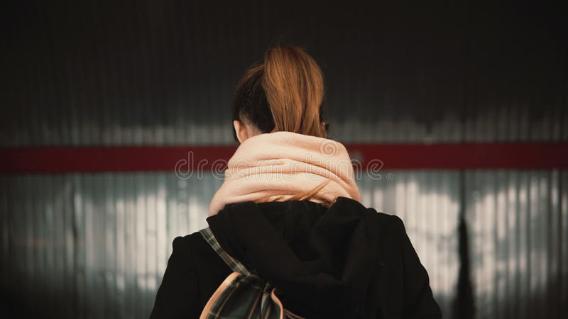 Young woman standing in the subway platform against the background of passing train. Girl waiting metro to go to job. royalty free stock images