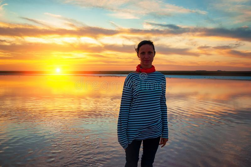Young woman standing at sunset by the water, beautiful reflection on the water from the sky royalty free stock photography